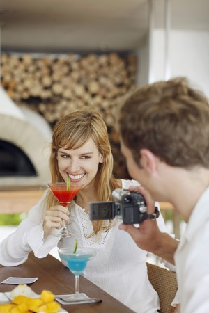 Man using video camera to record woman holding cocktail drink photo