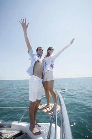 Couple standing at the tip of the yacht with arms raised photo