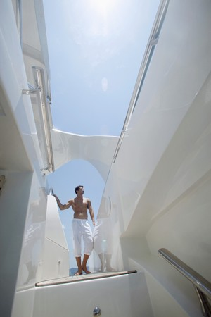 Man standing on yacht deck, looking away