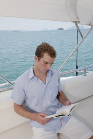 Man reading book on yacht Stock Photo - 7478204