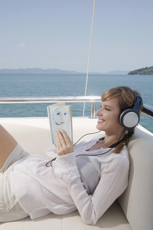 Woman listening to music while reading book on yacht photo