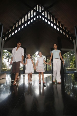 Family walking into resort while holding hands Stock Photo - 7478260