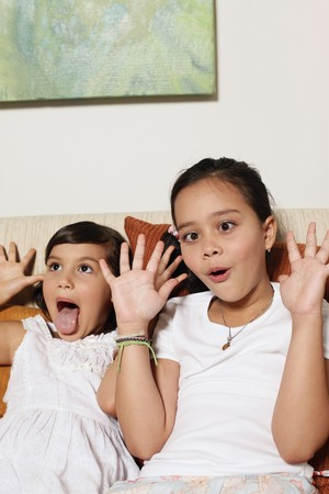 Girls making silly faces with hand gestures photo