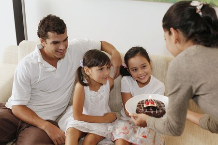 Woman surprising girl with chocolate cake, family sitting in the living room Stock Photo - 7478230