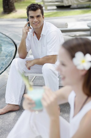 Man talking on the phone, woman drinking cocktail photo