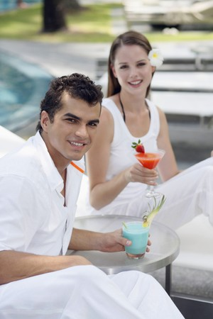 Man and woman on lounge chairs with their drinks Stock Photo - 7534758