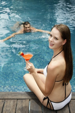 Woman with glass of cocktail sitting by the pool side, man swimming towards woman photo