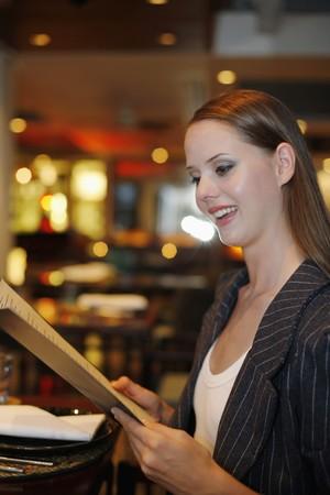 Woman reading menu in restaurant photo