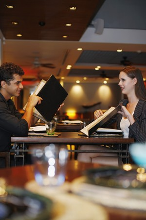 eastern european ethnicity: Man and woman reading menu in restaurant Stock Photo