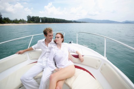Man and woman resting on speedboat photo