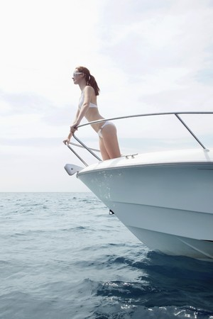 Woman standing at bow of speedboat photo