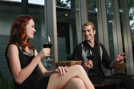 australian ethnicity: Man and woman holding glasses of red wine while chatting