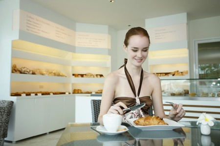 Woman enjoying breakfast of pastry and coffee at bakery Stock Photo - 7534501