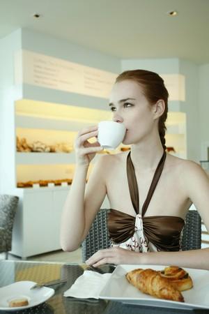 Woman enjoying breakfast and drinking coffee photo