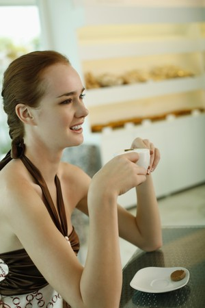 Woman enjoying a cup of coffee at bakery photo
