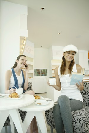 Woman reading book while having coffee, another woman is on the phone Stock Photo - 7534791