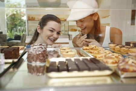 display case: Women looking through display case at variety of cakes and tarts Stock Photo