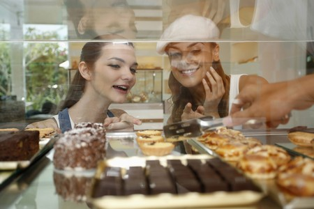 display case: Women choosing cakes and tarts from display case