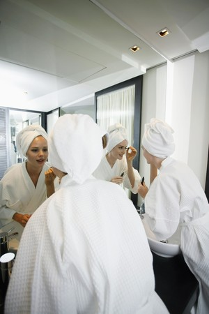 Women applying make-up in bathroom, looking at mirror photo
