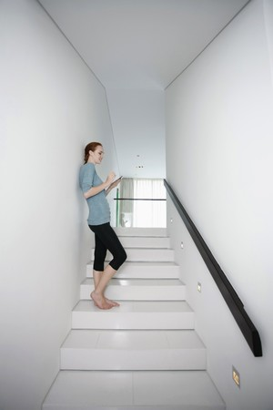 Woman text messaging while sitting on stairs photo