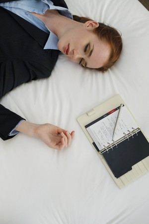 view of a comfortable bedroom: Businesswoman lying down on bed with organizer beside her Stock Photo