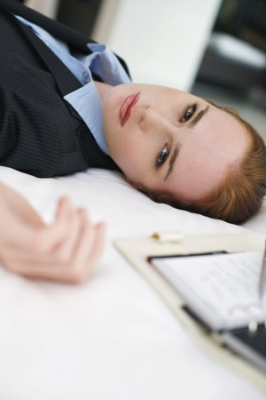 Businesswoman lying down on bed with organizer beside her Stock Photo - 7534496