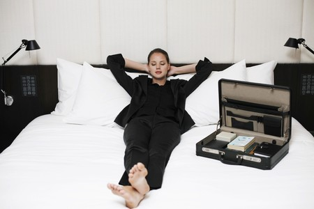 recline: Businesswoman relaxing on bed with briefcase at the side