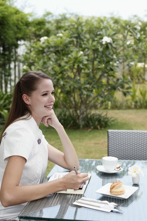 Woman writing in organizer while having breakfast outdoors Stock Photo - 7534966