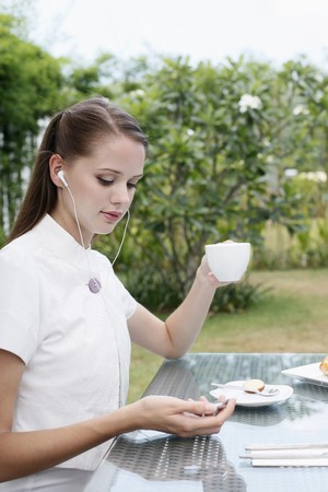 Woman listening to portable mp3 player while having coffee photo