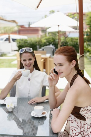 Woman talking on the phone while her friend is enjoying coffee photo