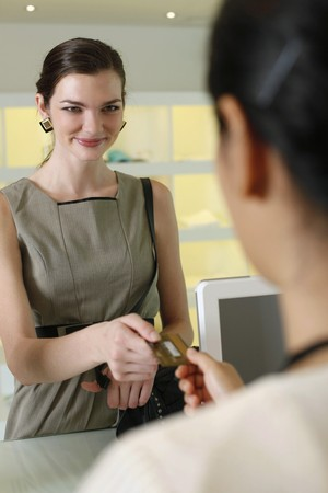 Woman handing credit card to cashier Stock Photo - 7534802