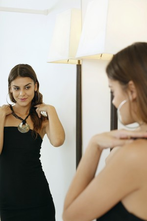 Woman trying on necklace in front of mirror photo