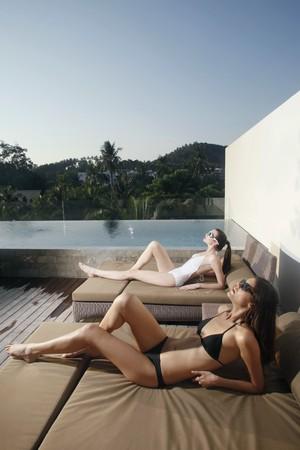 Women in bikini relaxing on lounge chair photo