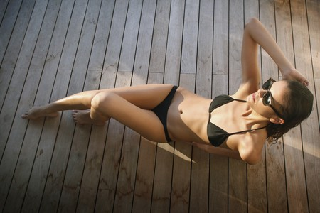 Woman in bikini sunbathing on wooden deck Stock Photo - 7534922