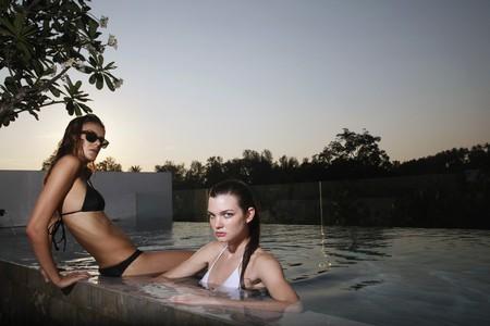 Women in bikini relaxing at the edge of pool Stock Photo - 7534762