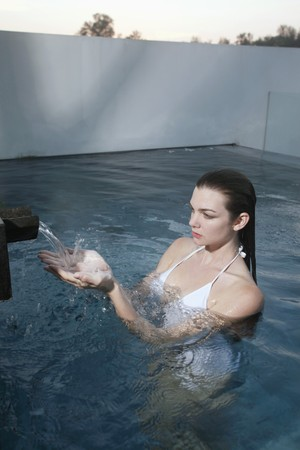 Woman with hand under running water in pool photo