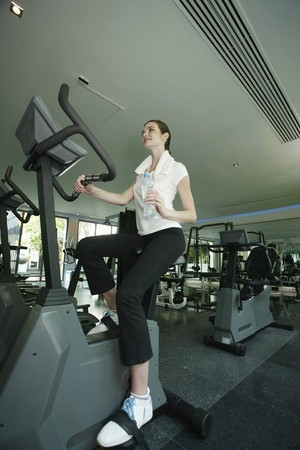 Woman holding a bottle of water while exercising in the gymnasium Stock Photo - 7534991