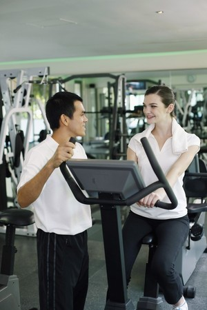 Personal trainer helping woman exercising in gymnasium photo