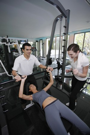 Personal trainer helping woman exercising in gymnasium, friend giving support photo