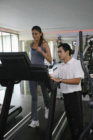 Woman running on treadmill, personal trainer watching Stock Photo - 7534896