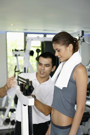Woman standing on weight scale, personal trainer checking her weight Stock Photo - 7534760