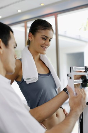 Woman standing on weight scale, personal trainer checking her weight