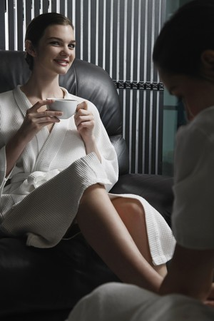 spa pedicure: Woman enjoying a cup of tea while getting a foot massage