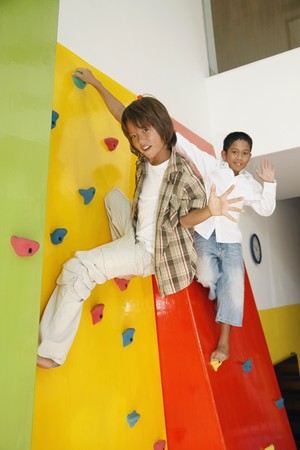 Boys climbing rock wall photo