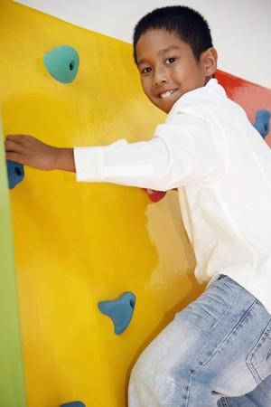 Boy climbing rock wall Stock Photo - 7534895