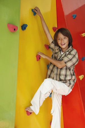 Boy climbing rock wall Stock Photo - 7534754