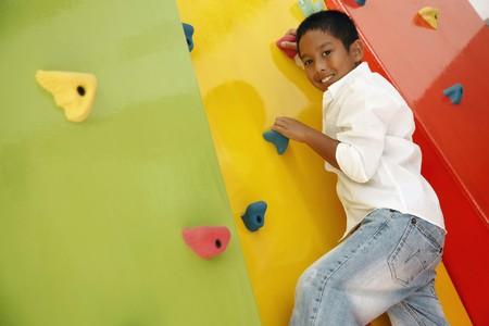 climbing sport: Boy climbing rock wall