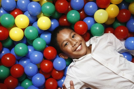 Boy lying in ball pool photo