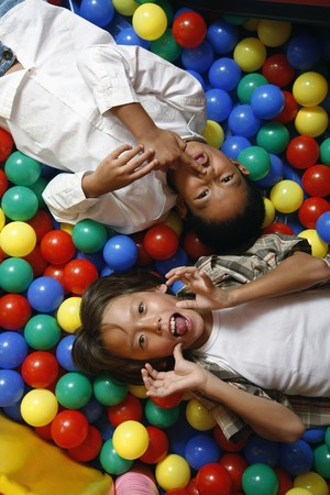 Boys in ball pool, making funny faces photo