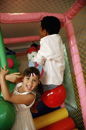 Children playing with rope swing indoors photo